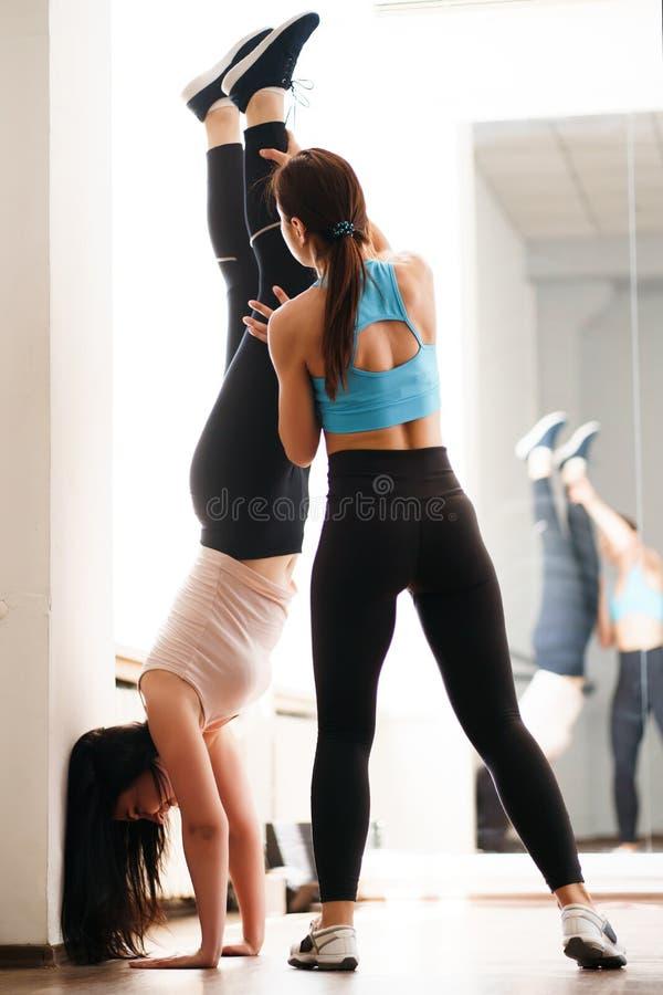 Instrutor que ajuda a mulher desportiva a fazer o pino foto de stock