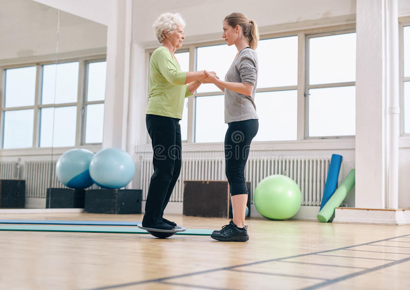 Instrutor que ajuda a mulher superior que exercita com um equilíbrio do bosu imagens de stock