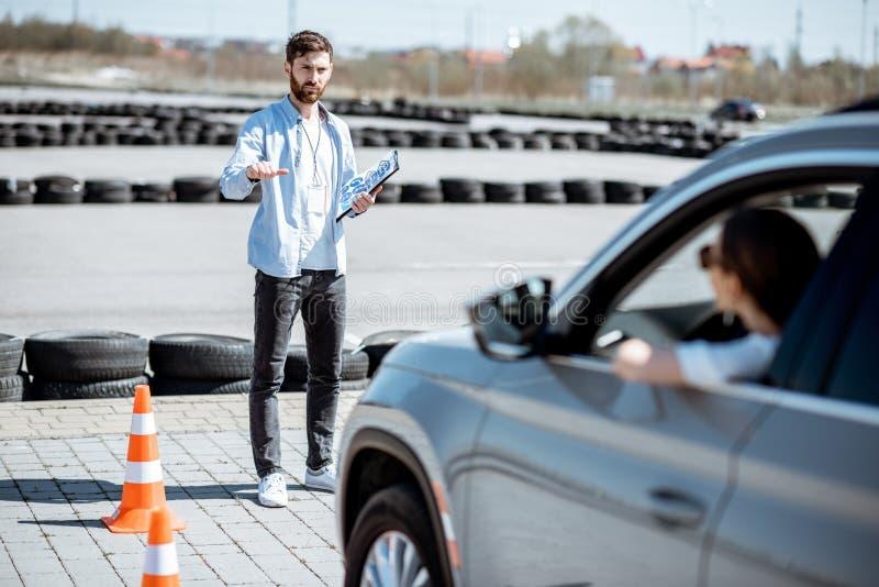 Instrutor que ensina para conduzir um carro no campo de treino imagens de stock royalty free