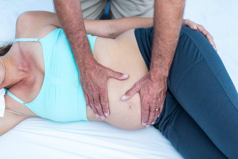 Instrutor que faz massagens a mulher gravida no gym imagem de stock