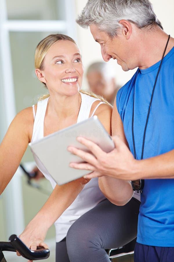 Instrutor que usa o tablet pc no fitness center imagens de stock