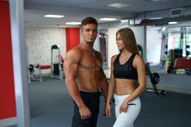 Instrutores da aptidão para os homens e as mulheres que levantam no gym imagens de stock