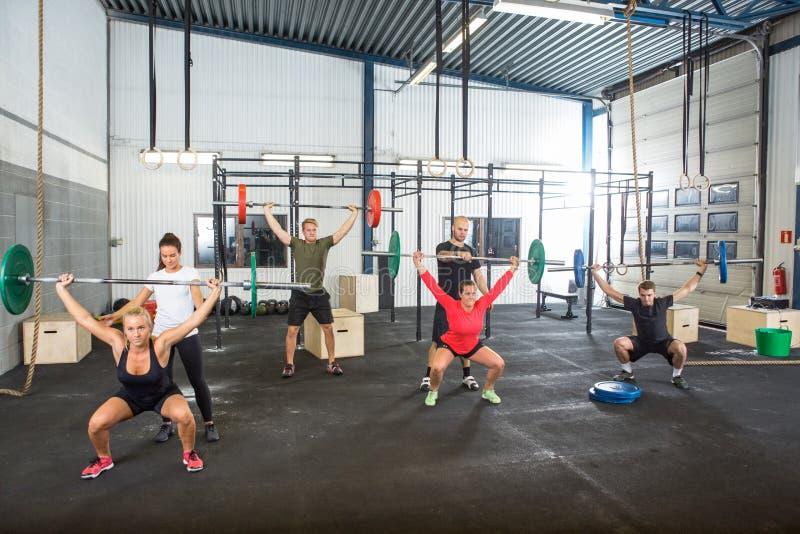 Instrutores que ajudam a atletas no exercício com foto de stock