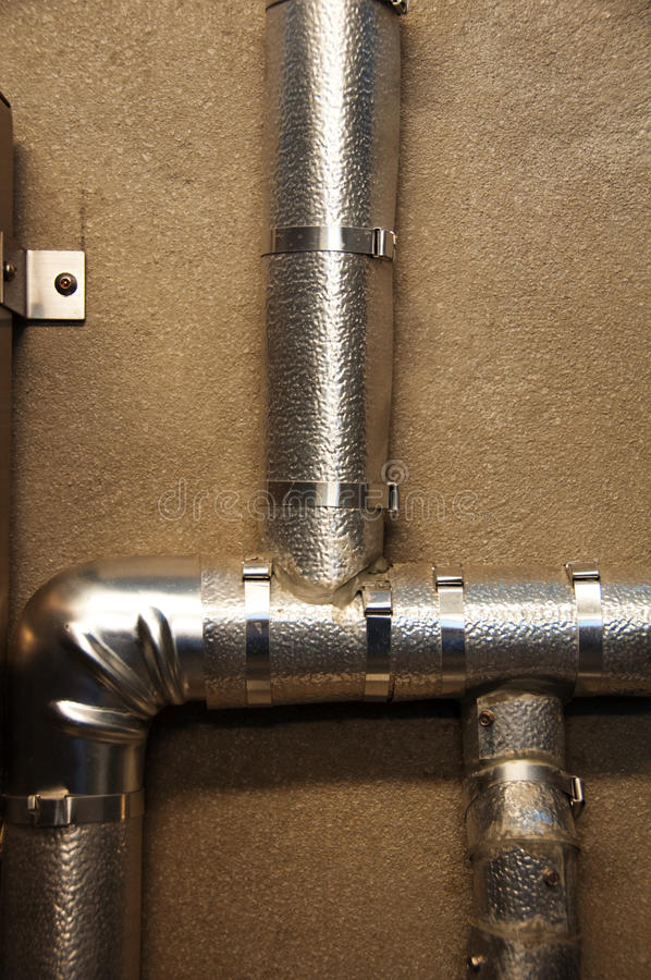 Insulated Pipe. Insulated plumbing pipes run in several directions along a bathroom wall stock image