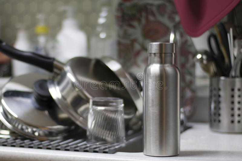 Insulated Stainless Bottle with utensils and sink kitchen background.  stock photos