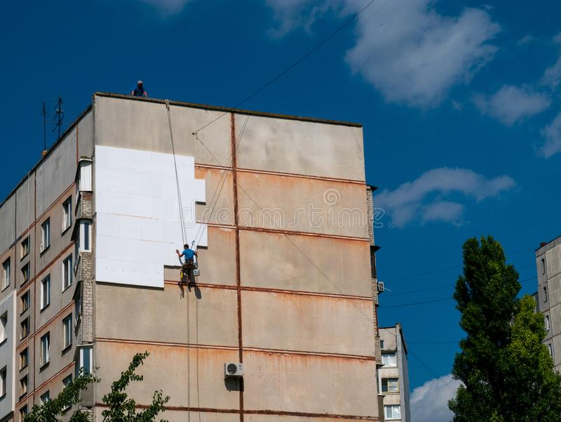 Insulation and Energy Saving Technology Concept. Worker Making B. Uilding with heat insulated facade stock photo