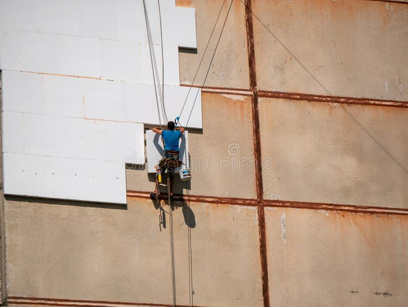Insulation and Energy Saving Technology Concept. Worker Making Building with heat insulated facade.  stock photos