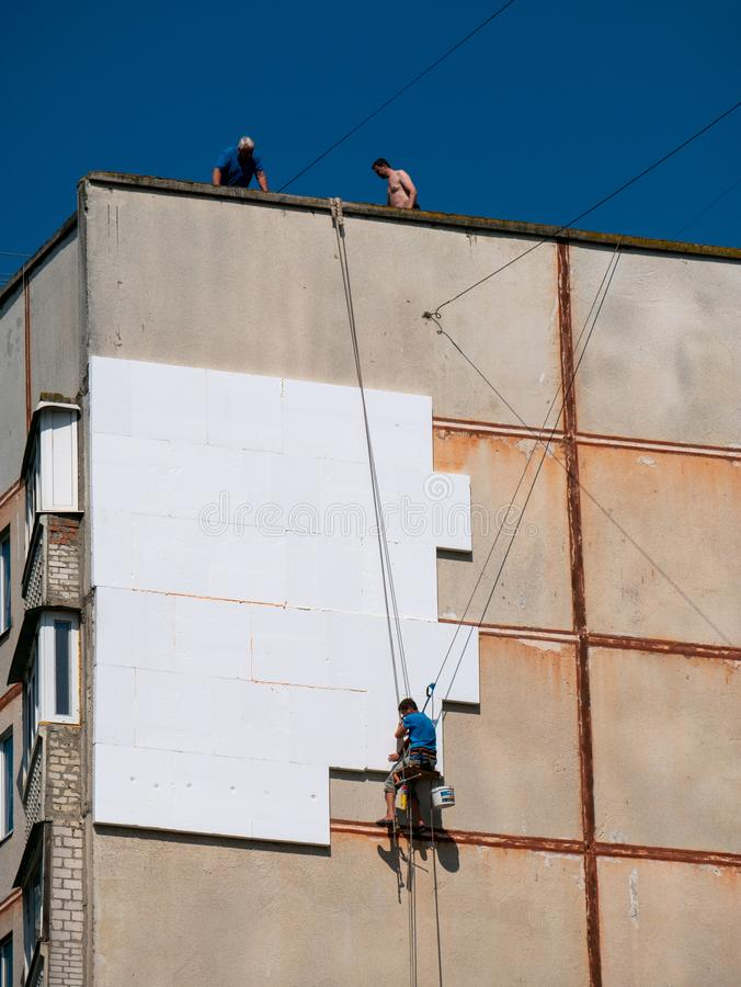 Insulation and Energy Saving Technology Concept. Worker Making Building with heat insulated facade.  stock photography