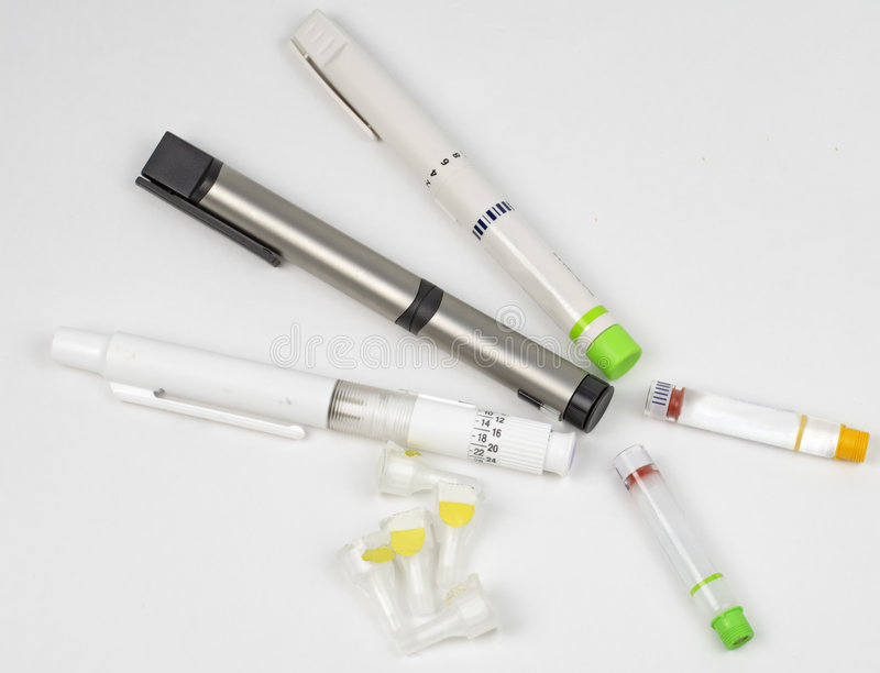 Insulin pens. Different types of pens for insulin administration.Also two types of insulin flasks and needles royalty free stock photography