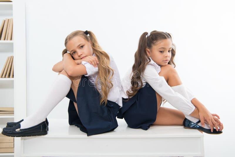 insulte insulte de deux petits enfants ou soeurs de filles à l'école petites filles dans l'uniforme scolaire images stock