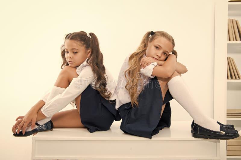 insulte insulte de deux petits enfants ou soeurs de filles ? l'?cole petites filles dans l'uniforme scolaire photos libres de droits