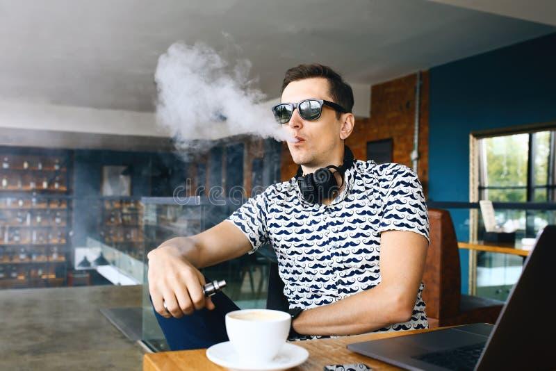 Insunglasse considerável novo do homem do moderno que senta-se no café com uma xícara de café, vaping e umas liberações uma nuvem imagem de stock