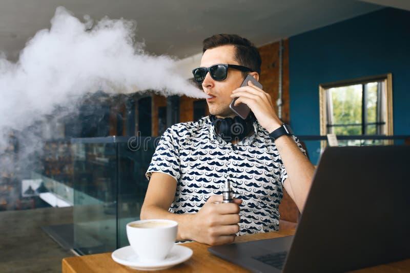 Insunglasse considerável novo do homem do moderno que senta-se no café com uma xícara de café, vaping e umas liberações uma nuvem fotos de stock royalty free
