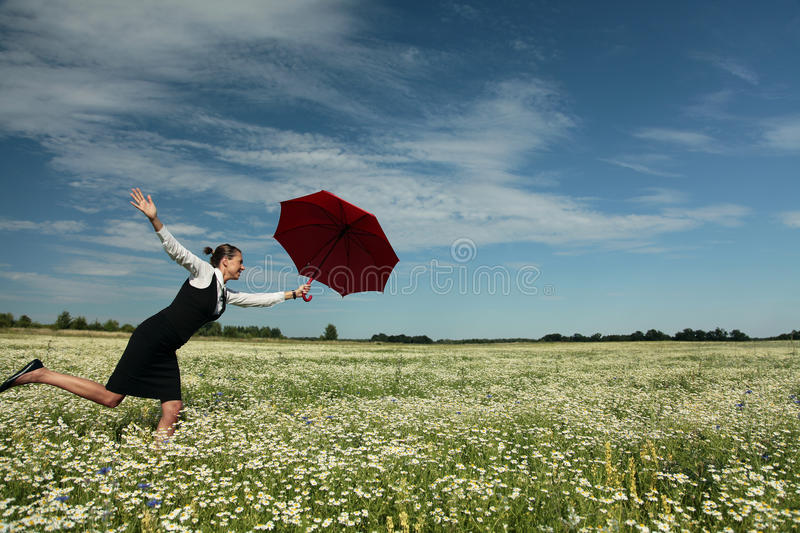 Insurance Agent. Protects you. Businesswoman with Red Umbrella on meadow royalty free stock image