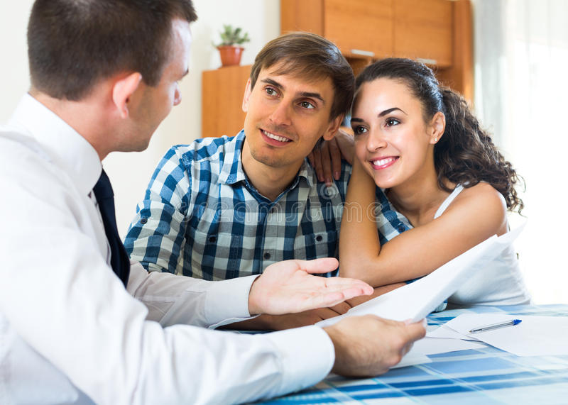 Insurance agent and couple indoors. Insurance agent consulting happy young couple in home interior stock photography