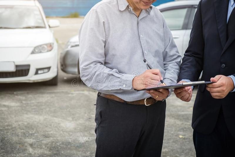 Insurance Agent examine Damaged Car and customer filing signature on Report Claim Form process after accident, Traffic Accident stock images