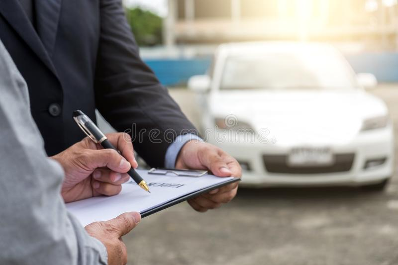 Insurance Agent examine Damaged Car and customer filing signature on Report Claim Form process after accident, Traffic Accident royalty free stock photo