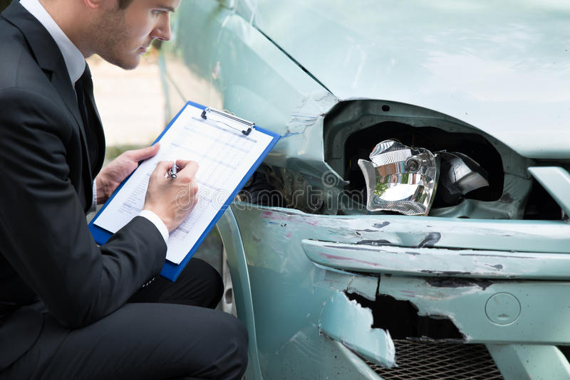 Insurance agent examining car after accident. Side view of writing on clipboard while insurance agent examining car after accident royalty free stock image