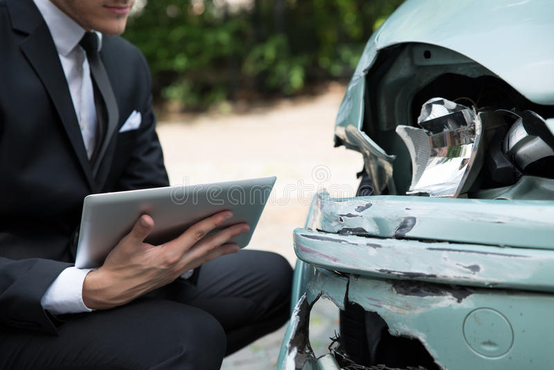 Insurance agent examining car after accident. Side view of writing on clipboard while insurance agent examining car after accident stock photography