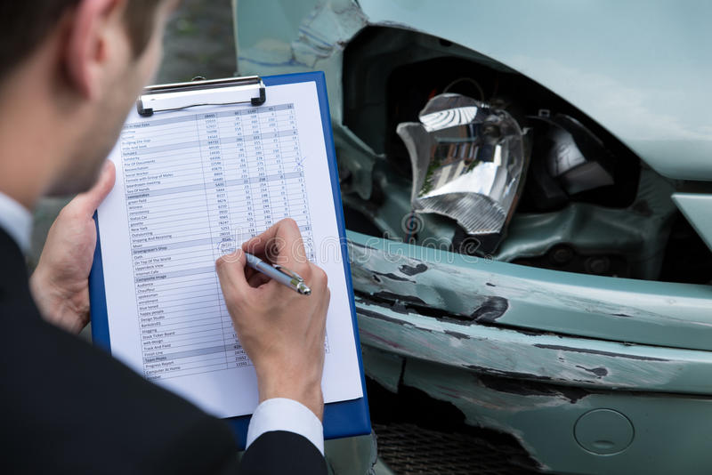 Insurance agent examining car after accident. Side view of writing on clipboard while insurance agent examining car after accident royalty free stock photos
