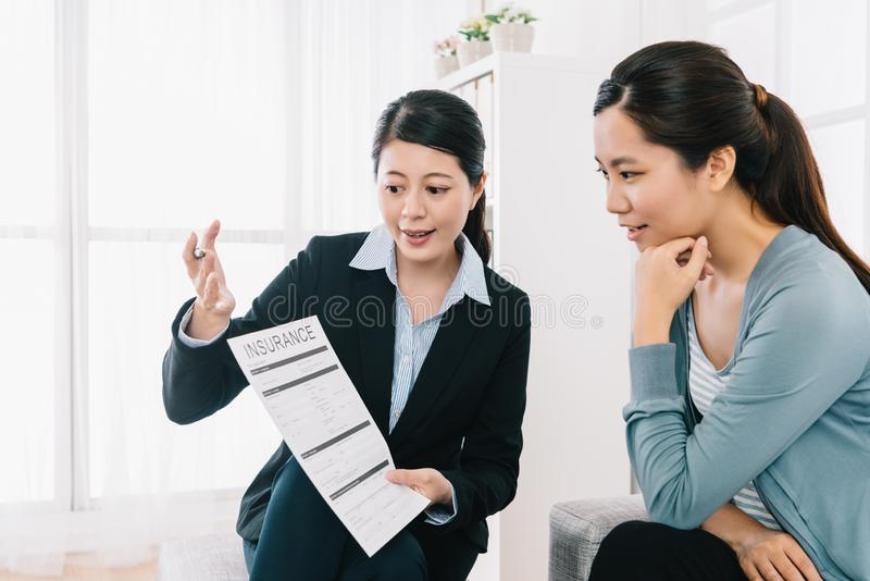 Insurance agent explaining the assurance planning. Professional insurance agent explaining the assurance planning to the shrewd housewife at home. Female Real royalty free stock photo