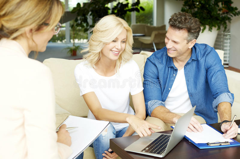 Insurance agent and her clients. Shot of a middle aged happy couple planning their future while consulting with insurance agent in their home stock images