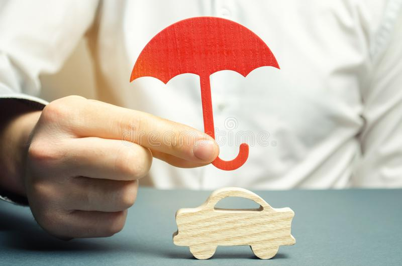 An insurance agent is holding a red umbrella over a miniature wooden car. Auto insurance concept. Vehicle protection. Insurance. Company services. Gesture of stock image