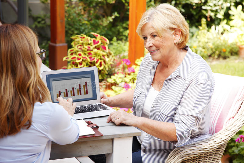Insurance agent. Portrait of businesswoman consulting with retired women at home. Insurance agent sitting in front of laptop and giving advise to senior woman stock photos