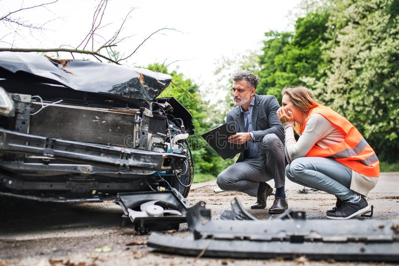 An insurance agent and a woman driver looking at the car on the road after an accident. An insurance agent and a women driver looking at the car on the road stock images