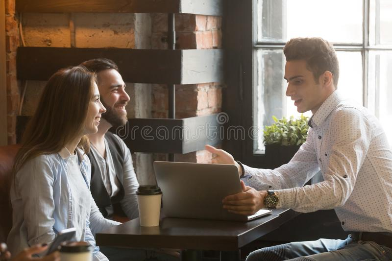 Insurance broker or salesman making offer to couple in cafe. Insurance broker or salesman making offer to young millennial couple using laptop in cafe, realtor stock photography