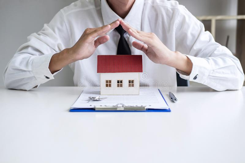 Insurance and care protection of house concept, businessman agent with protective gesture of small home model.  royalty free stock photo
