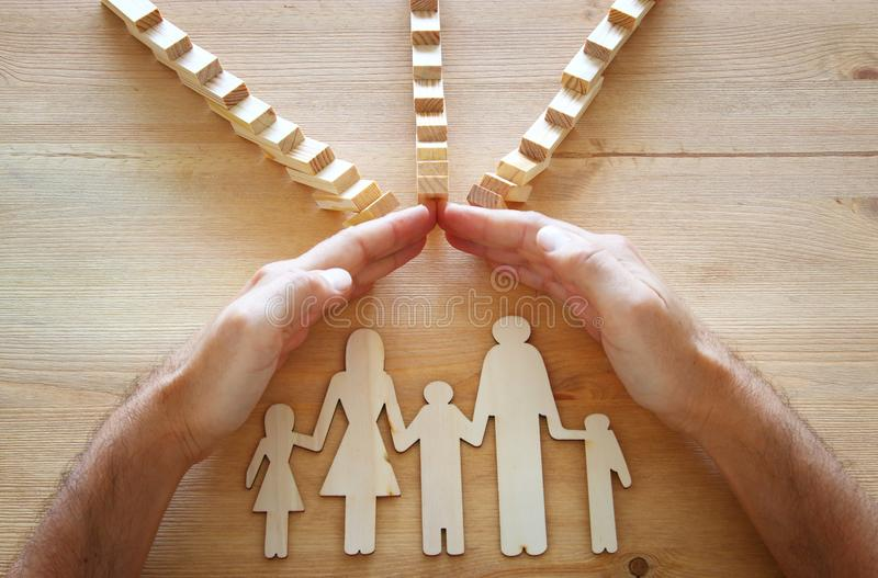 Insurance concept. Businessman protecting a family from domino effect. life, financial and health issues.  stock images