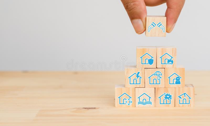 Insurance concept, hand man try to put the insurance to protect or cover home, homeowner, flood, earthquake, fire, explosion, ligh stock photography