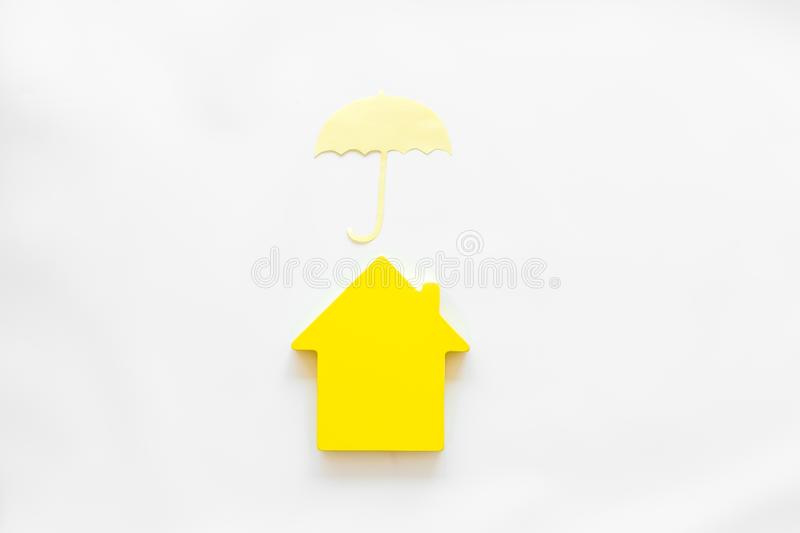 Insurance concept with house figure and umbrella on white background top view. Buy and insure house concept. Insurance concept with house figure and umbrella on royalty free stock images