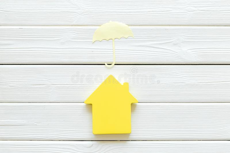 Insurance concept with house figure and umbrella on white wooden background top view. Buy and insure house concept. Insurance concept with house figure and stock photography