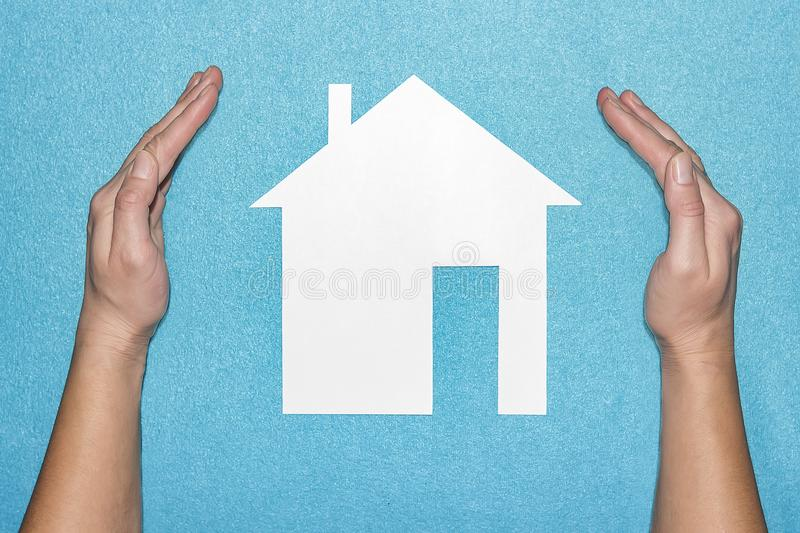 Insurance of house concept. Hands protects home. Paper house inside hands on blue background royalty free stock photography