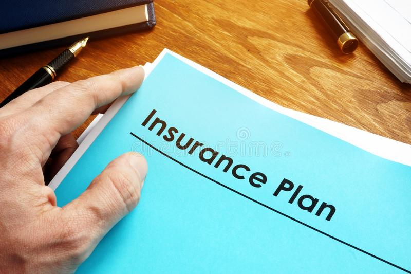 Insurance Plan policy papers on desk. Insurance Plan policy papers on wooden desk stock image