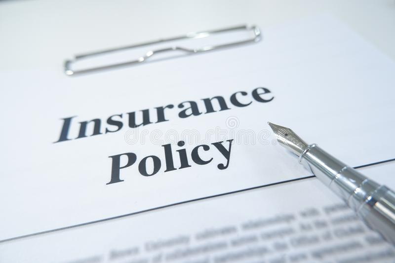 Insurance policy form and pen on desk in office showing risk concept. Life; Health, car, travel stock photography