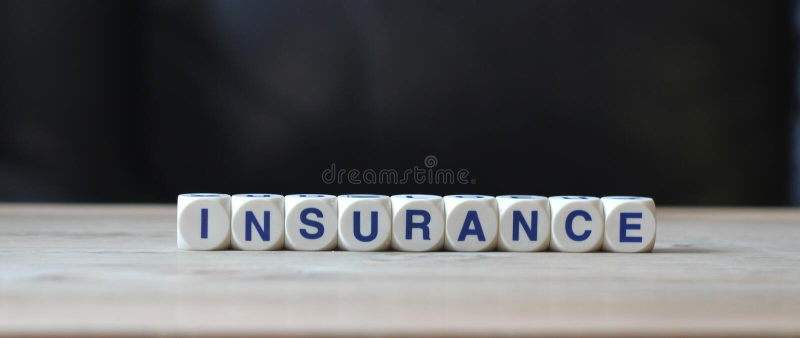 Insurance. White letter cubes on table and black background word insurance stock images