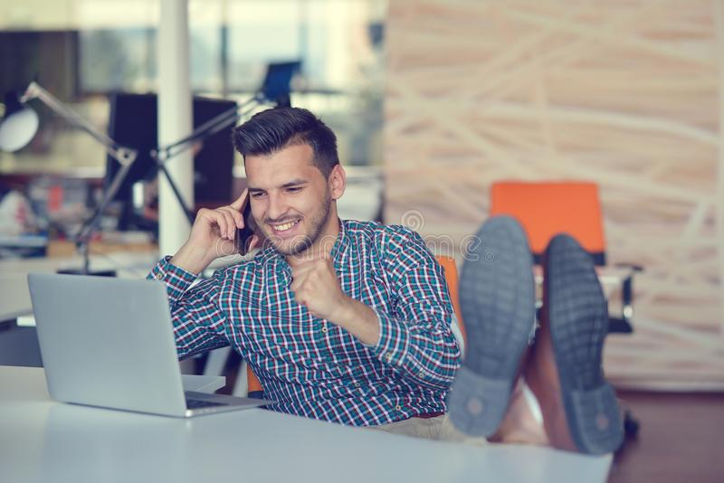 Intégral d'un jeune homme d'affaires occasionnel décontracté s'asseyant avec des jambes sur le bureau au bureau photographie stock libre de droits