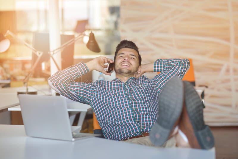 Intégral d'un jeune homme d'affaires occasionnel décontracté s'asseyant avec des jambes sur le bureau au bureau photos stock