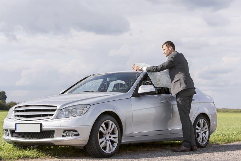 Intégral de la jeune carte de lecture d'homme d'affaires en la voiture à la campagne image stock