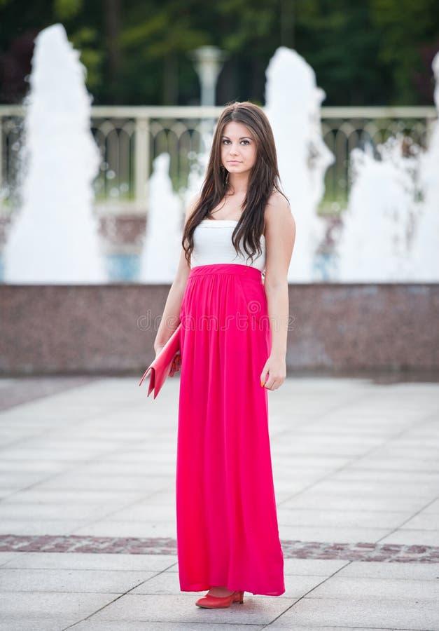 Intégral de la jeune femelle caucasienne avec la longue jupe rouge se tenant devant une fontaine extérieure images stock