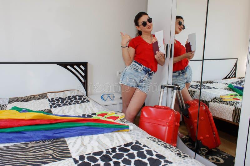 Intégral de la jeune femelle dans la position occasionnelle avec la valise de voyage, le passeport de participation et les billet image stock