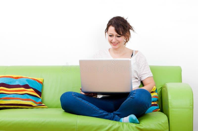 Intégral de la jeune femme heureuse à l'aide de l'ordinateur portable tout en se reposant sur le sofa vert images libres de droits
