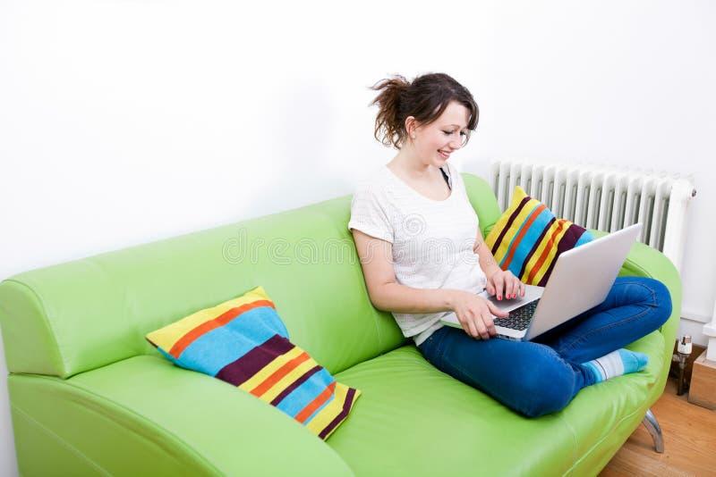 Intégral de la jeune femme heureuse à l'aide de l'ordinateur portable tout en se reposant sur le sofa vert photos stock