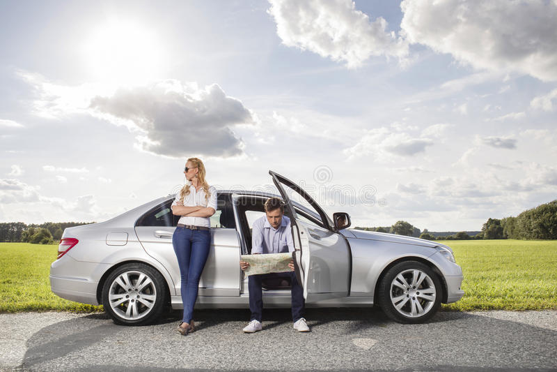 Intégral de la jeune femme regardant partie tandis que carte de lecture d'homme dans la voiture la campagne images stock