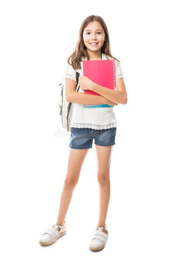 Intégral de la petite fille hispanique tenant et tenant des livres photos libres de droits