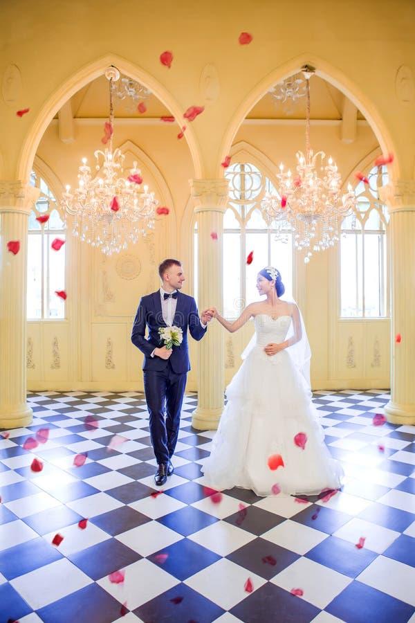 Intégral des couples élégants de mariage regardant l'un l'autre tout en marchant dans l'église photographie stock libre de droits