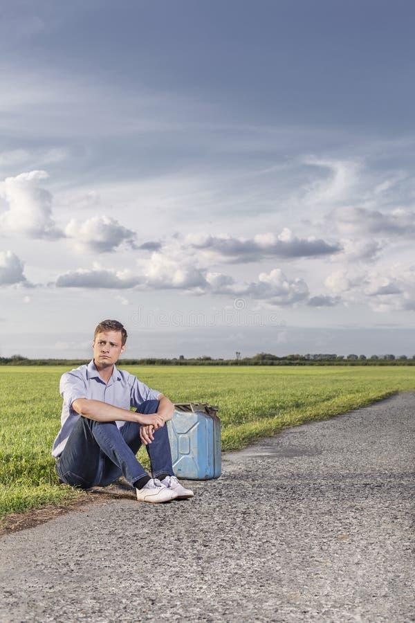Intégral du jeune homme avec l'essence vide pouvez en se reposant par la route de campagne photos libres de droits